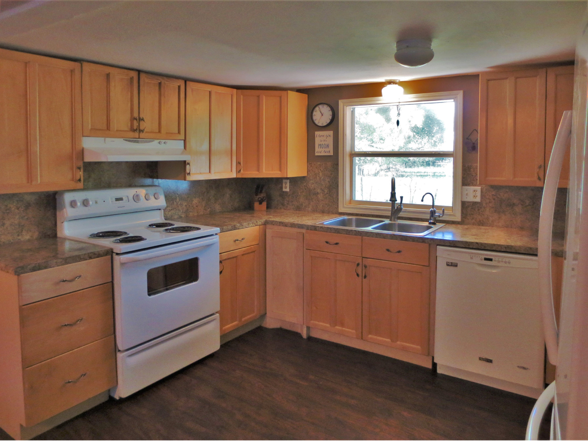 Updated Kitchen viewed from right. TWO HOMES on a HALF ACRE in MEDINA in the Texas Hill Country. Listed for sale with Gail Stone Realty in Bandera, TX. 830-796-4640