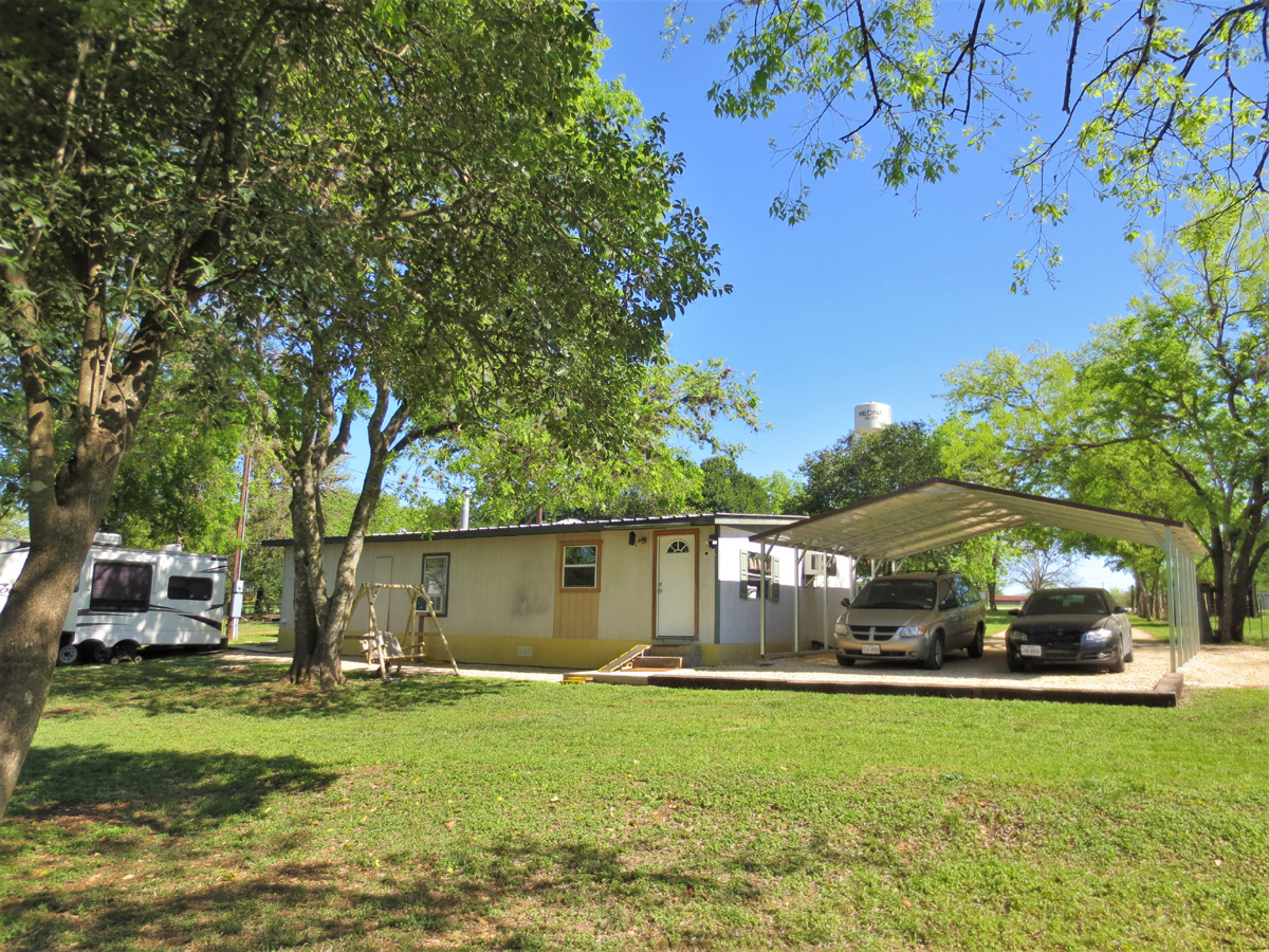 Back of home and carport. TWO HOMES on a HALF ACRE in MEDINA in the Texas Hill Country. Listed for sale with Gail Stone Realty in Bandera, TX. 830-796-4640