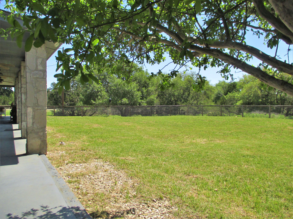 View of the other side of the back yard and fence at 503 Oak Bend.