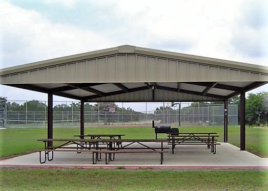 View of covered pavilion with picnic tables and BBQ near tennis courts