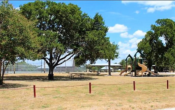 Playground and picnic area in the shade at the Bandera River Ranch.