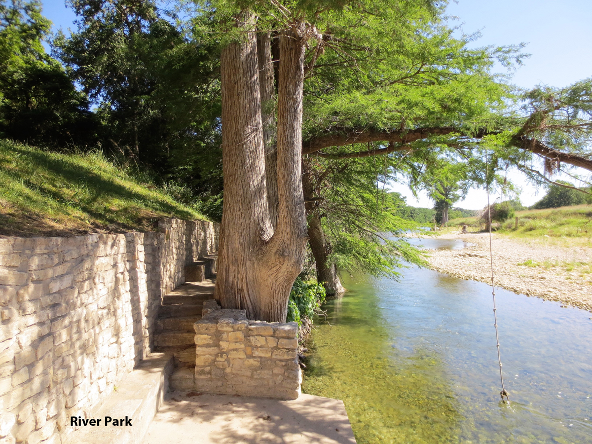 Steps behind cypress trees along the Medina River at the Comanche Cliffs River Park.