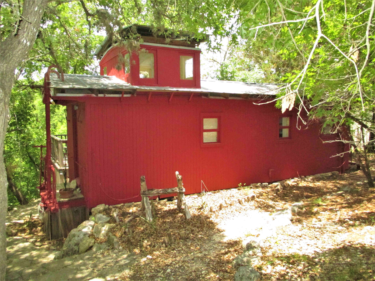 TREETOP CABOOSE on the RIVER on 1 ACRE fronting the HIGHLAND WATERS park along the sparkling MEDINA RIVER. Listed  for sale with Gail Stone Realty in Bandera, Texas. 830-796-4640 / H0236
