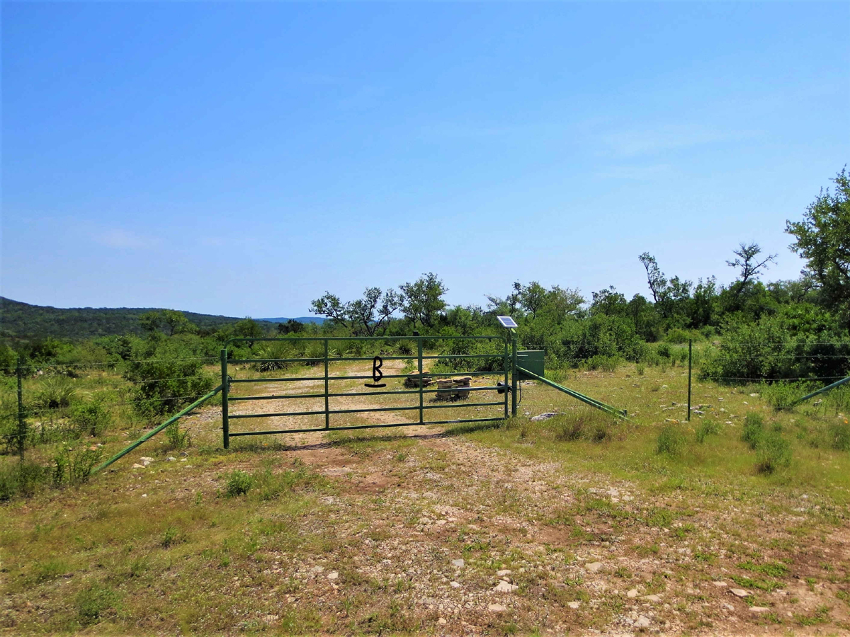 View of far off hills. Trees and native plants and front gate in the foreground